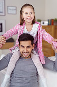 Happy little girl sitting on her fathers shoulders as they relax together at home on a sofa both smiling happily at the camera