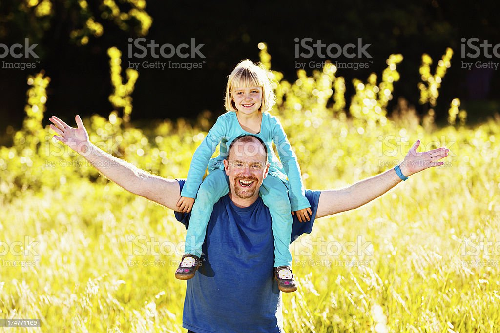 Happy little girl sitting on laughing father's shoulders in field stock photo