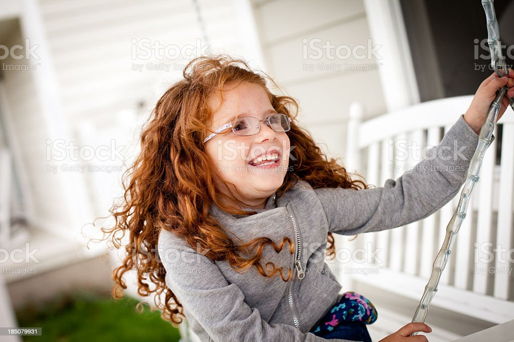 Happy Little Girl Sitting Outside on Porch Swing royalty-free stock photo
