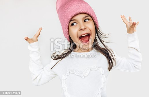 istock Happy little girl smiling broadly with mouth open wide, looking to one side, wearing white sweater and knitted pink hat, hands rise up, posing over studio gray wall. Cute child waiting for Christmas. 1168892021