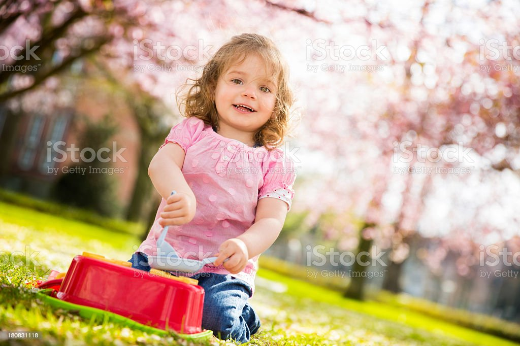 Happy little girl smiling in the park stock photo