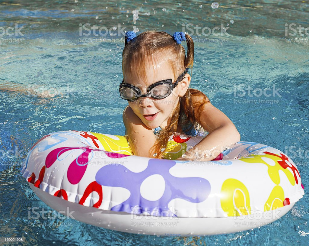 happy little girl splashing around in the pool royalty-free stock photo