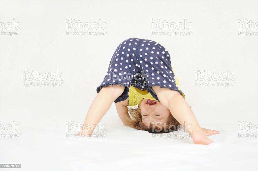 Happy little girl standing on head upside down stok fotoğrafı