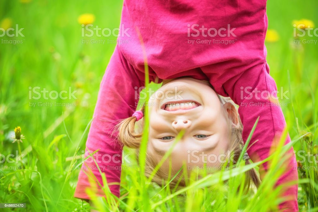 Happy little girl standing upside down on grass in summer park stock photo
