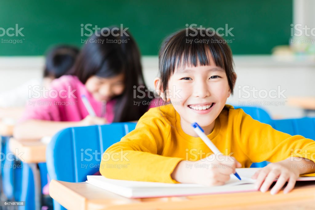 happy little girl student studying in the classroom stock photo