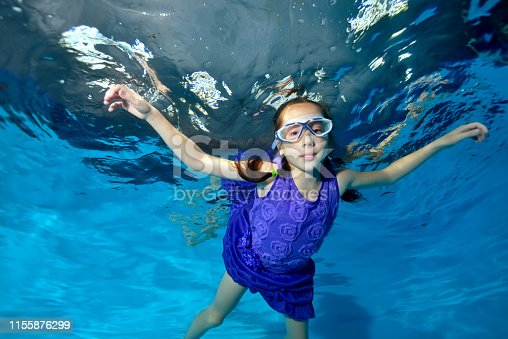 A cute little girl under water at the bottom of the pool with her eyes open in a red dress smiles and poses for the camera with her arms outstretched on a blue background. Portrait. Vertical view.