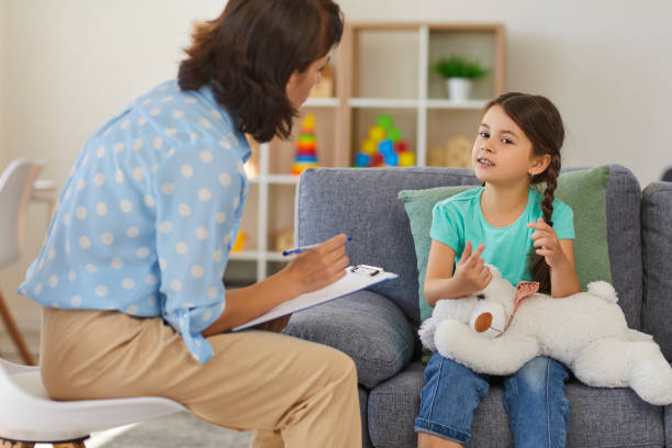 Happy little girl telling story to child psychologist during therapy session in cozy modern office stock photo