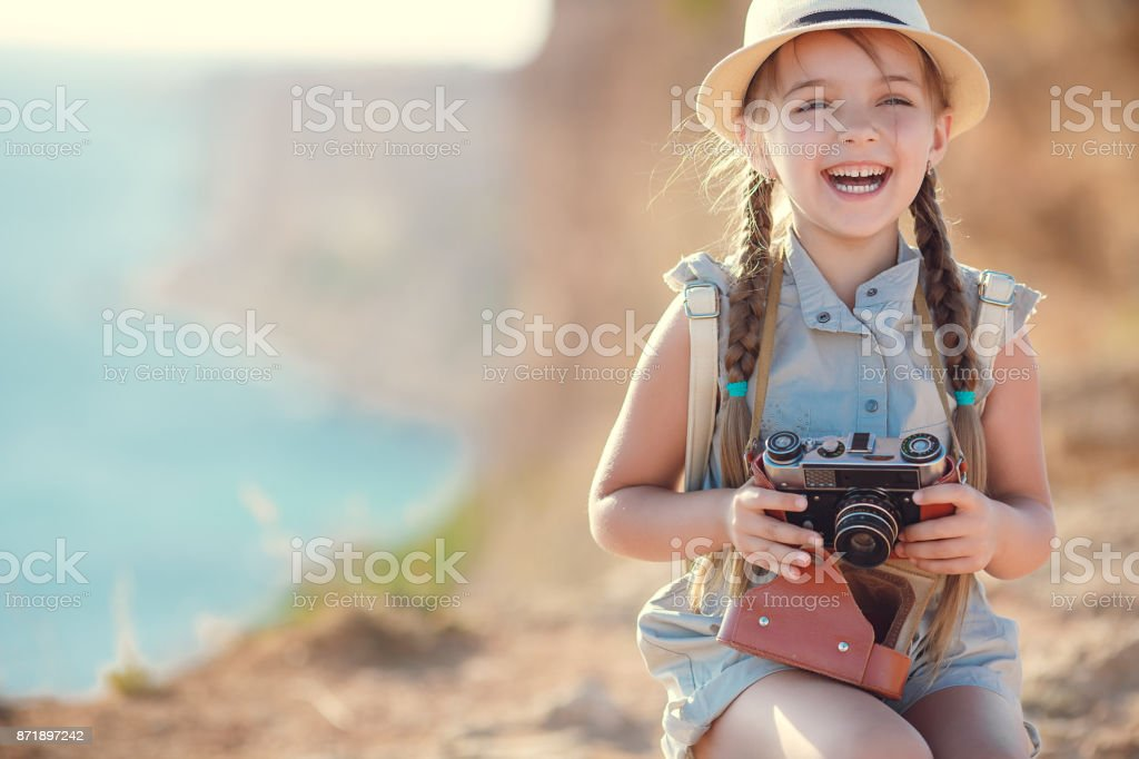 Happy little girl travels with a vintage suitcase and an old camera stock photo
