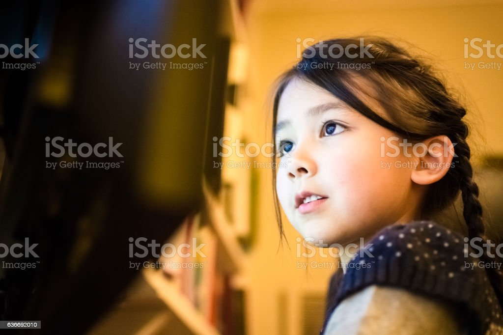Happy little girl using a computer at home stock photo