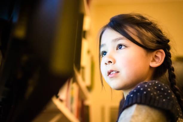 happy little girl using a computer at home - lernfortschrittskontrolle stock-fotos und bilder