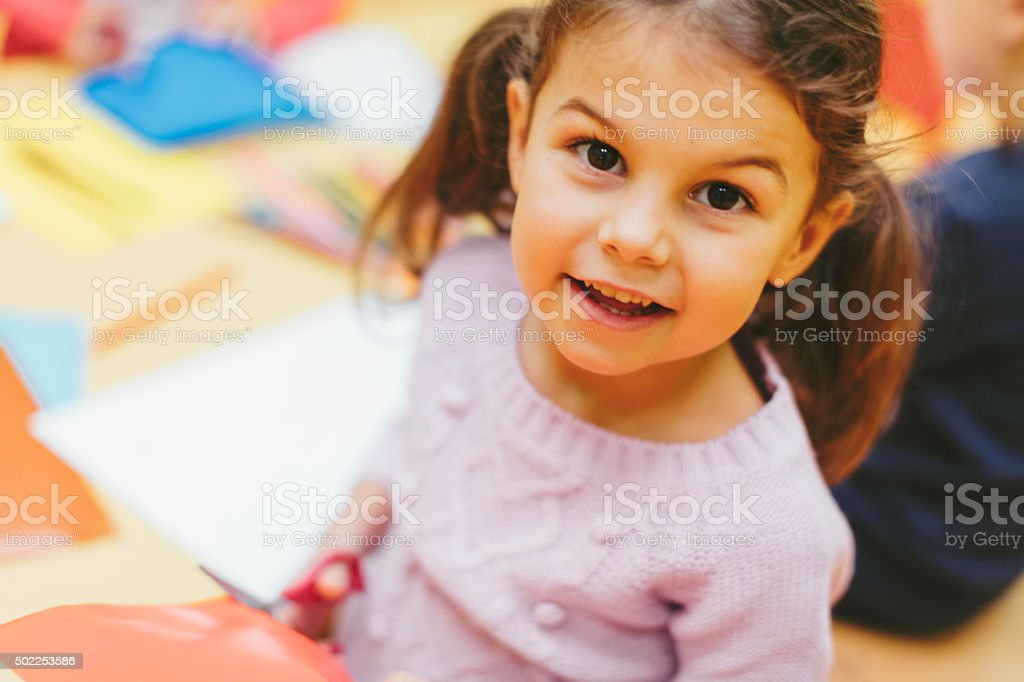 Happy Little Girl Using Scissors. stock photo