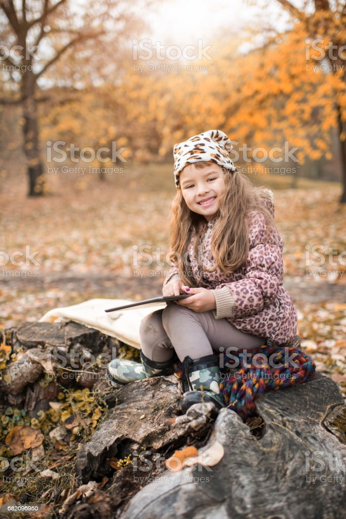 Happy little girl using touchpad in autumn day. stock photo