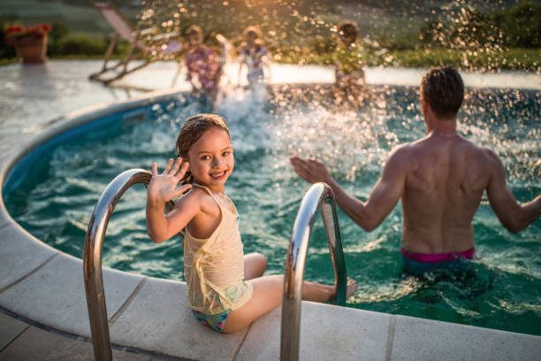 Happy little girl waving at the poolside. Happy small girl sitting at the poolside and waving to camera while her father is in the pool. backyard pool stock pictures, royalty-free photos & images