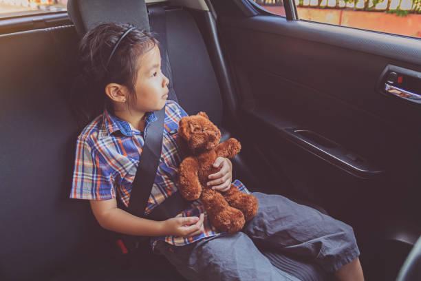 bonne petite fille portant des ceintures de sécurité en voiture - child car sleep photos et images de collection