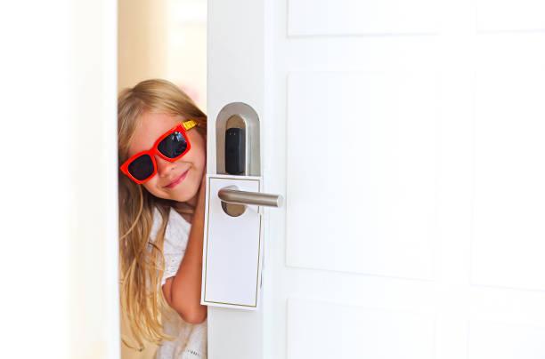 Niña feliz usando gafas de sol en la habitación del hotel abriendo la puerta - foto de stock
