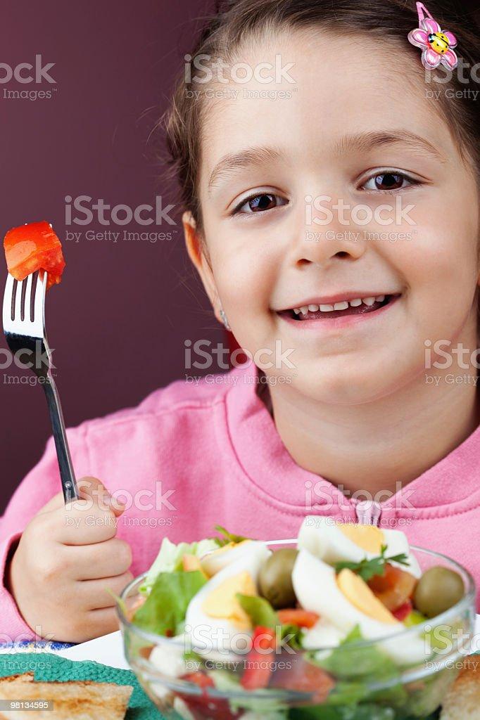 Bambina felice con una ciotola di insalata foto stock royalty-free
