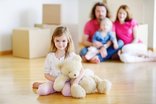 happy little girl with a toy in her new home - happy mom packing some toys stock photos and pictures