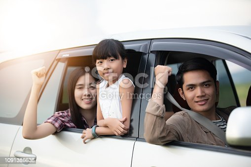 849398784 istock photo Happy little girl  with asian family sitting in the car for enjoying road trip and summer vacation in camper van 1091386636