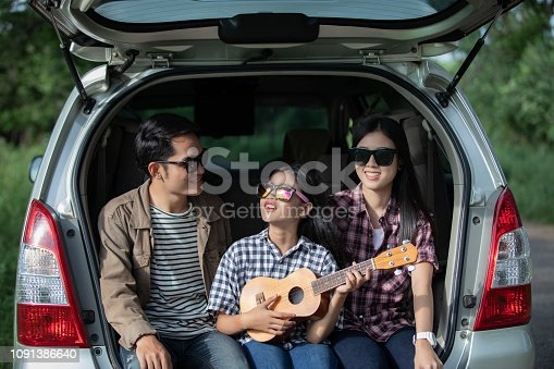 849398784 istock photo Happy little girl  with asian family sitting in the car for enjoying road trip and summer vacation in camper van 1091386640