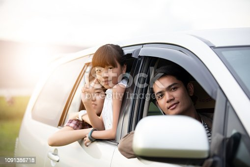 849398784 istock photo Happy little girl  with asian family sitting in the car for enjoying road trip and summer vacation in camper van 1091386718