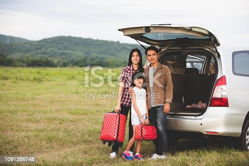 849398784 istock photo Happy little girl  with asian family sitting in the car for enjoying road trip and summer vacation in camper van 1091386748
