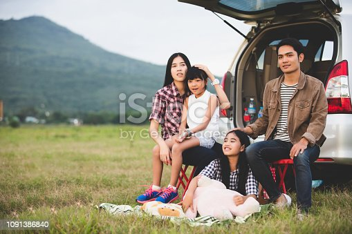 849398784 istock photo Happy little girl  with asian family sitting in the car for enjoying road trip and summer vacation in camper van 1091386840