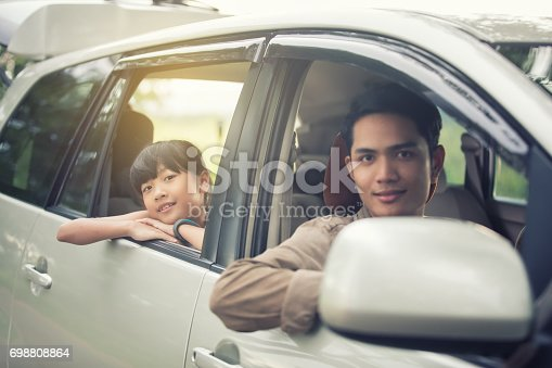 849398784 istock photo happy little girl  with asian family sitting in the car for enjoying road trip and summer vacation 698808864