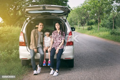 849398784 istock photo happy little girl  with asian family sitting in the car for enjoying road trip and summer vacation 698808884