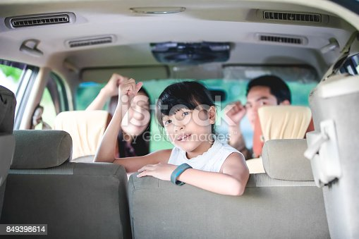 849398784 istock photo Happy little girl  with asian family sitting in the car for enjoying road trip and summer vacation in camper van 849398614