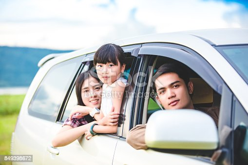 849398784 istock photo Happy little girl  with asian family sitting in the car for enjoying road trip and summer vacation in camper van 849398672