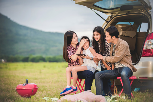 istock Happy little girl  with asian family sitting in the car for enjoying road trip and summer vacation in camper van 849398784