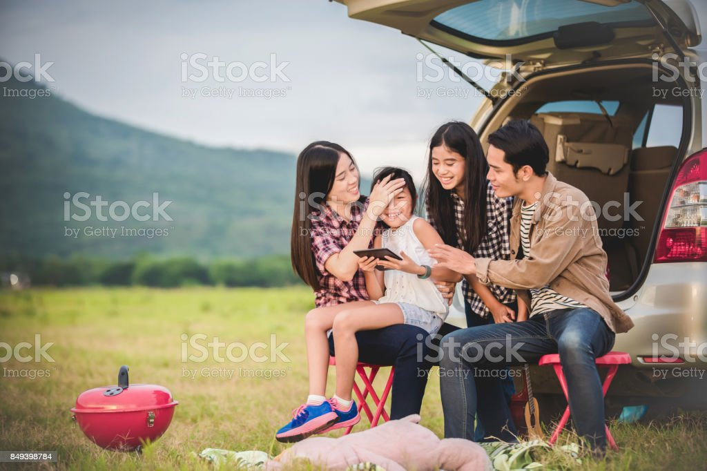 Happy little girl  with asian family sitting in the car for enjoying road trip and summer vacation in camper van stock photo