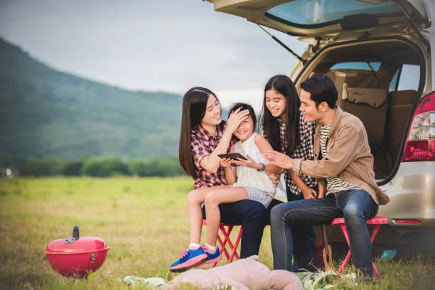 happy little girl  with asian family sitting in the car for enjoying road trip and summer vacation in camper van - asian travel in car stock photos and pictures