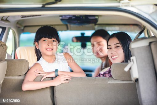 849398784 istock photo Happy little girl  with asian family sitting in the car for enjoying road trip and summer vacation in camper van 849402990