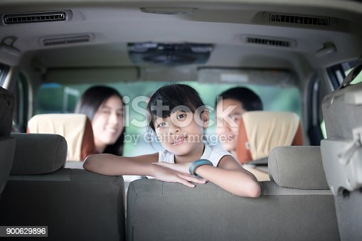 849398784 istock photo Happy little girl  with asian family sitting in the car for enjoying road trip and summer vacation in camper van 900629896