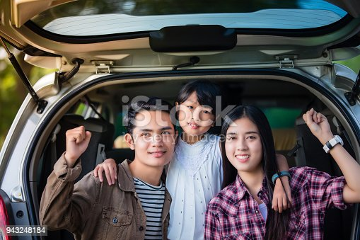 849398784 istock photo Happy little girl  with asian family sitting in the car for enjoying road trip and summer vacation in camper van 943248184