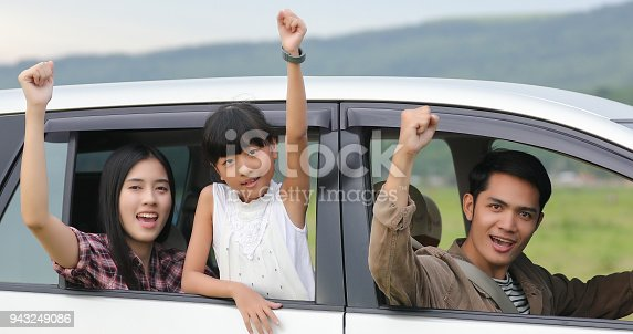 849398784 istock photo Happy little girl  with asian family sitting in the car for enjoying road trip and summer vacation in camper van 943249086