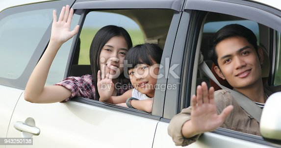 849398784istockphoto Happy little girl  with asian family sitting in the car for enjoying road trip and summer vacation in camper van 943250138
