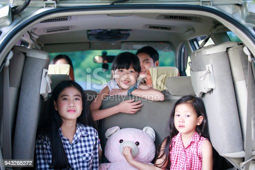 849398784 istock photo Happy little girl  with asian family sitting in the car for enjoying road trip and summer vacation in camper van 943265272