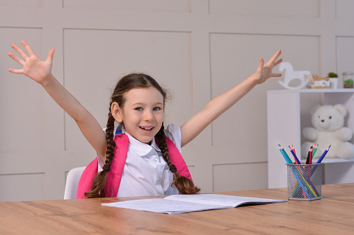 Happy little girl with backpack on her back rejoices back to school after distance learning at home. School concept. Back to School