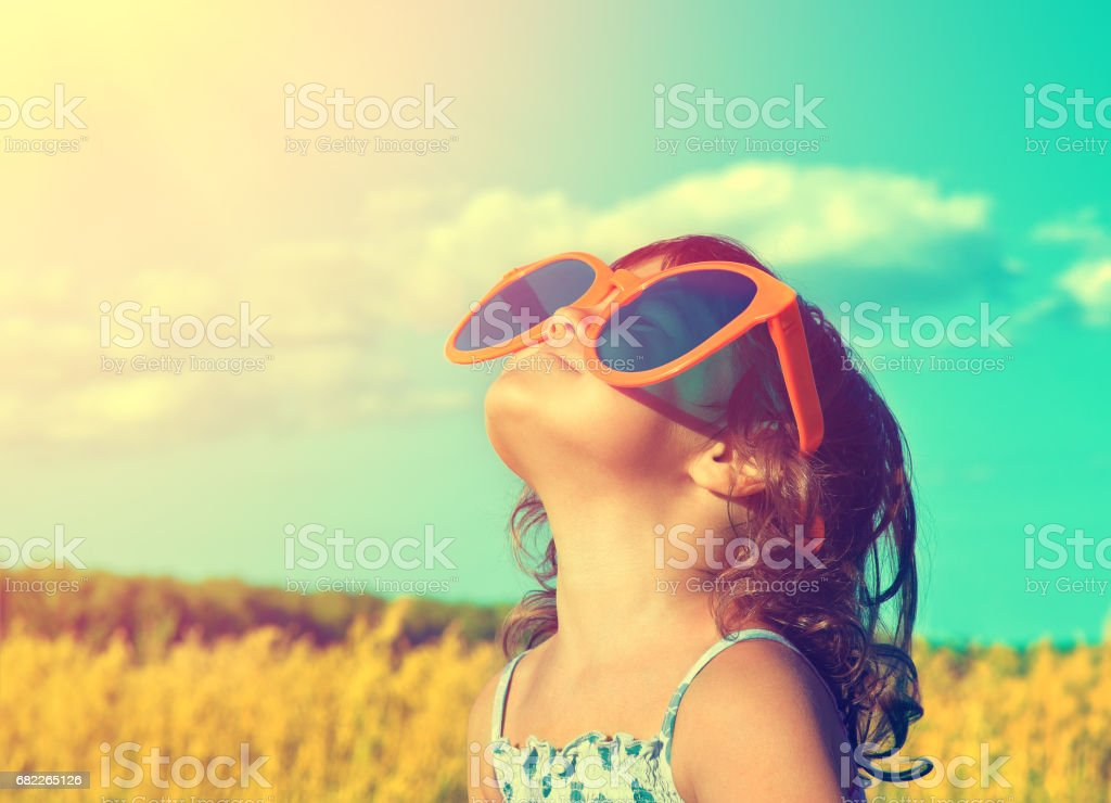 Happy little girl with big sunglasses looking at the sun in the wheat field in summer – Foto
