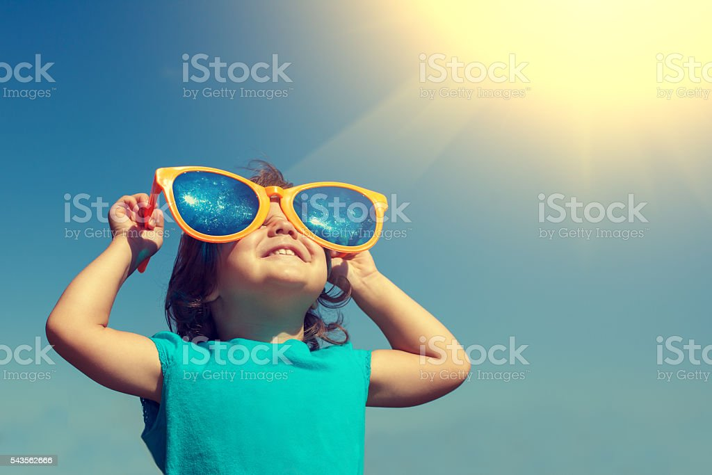Happy little girl with big sunglasses looking at the sun - 免版稅一個人圖庫照片