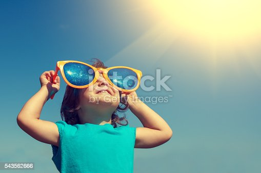 istock Happy little girl with big sunglasses looking at the sun 543562666