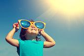 幸せそうな少女は大きなサングラスで、太陽の下である