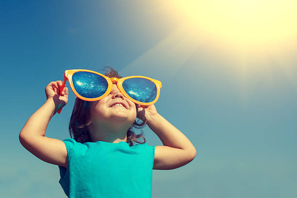 happy little girl with big sunglasses looking at the sun - aydınlık stok fotoğraflar ve resimler