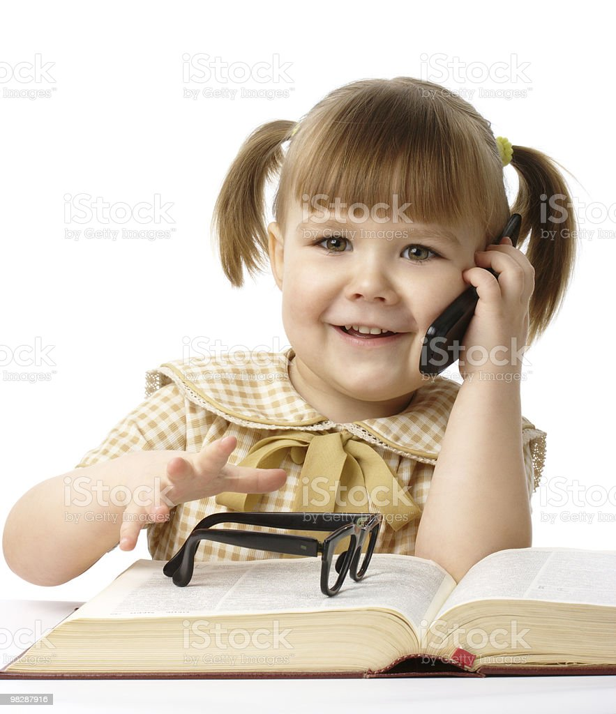 Happy little girl with book and a cell phone royalty-free stock photo
