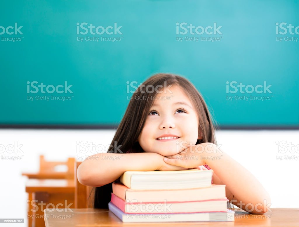 happy little girl with books and thinking in classroom stock photo