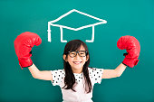 happy little girl with  boxing gloves and graduation concept