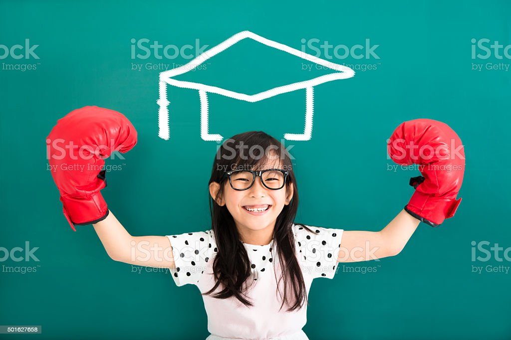 happy little girl with  boxing gloves and graduation concept stock photo