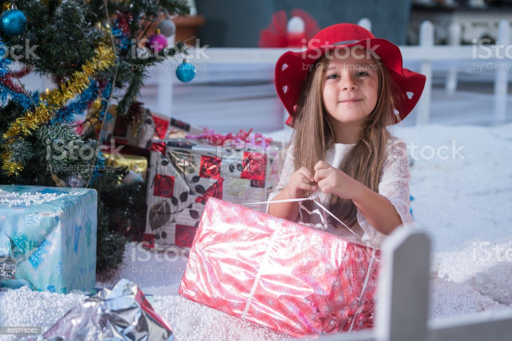 happy little girl with Christmas gift and Christmas tree royalty-free stock photo